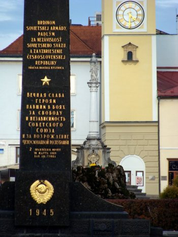 Banska_Bystrzyca_Plac_SNP_czarny_obelisk_poswiecony_Armii_Czerwonej_Kolumna_Maryjna_i_Wieza_Zegarowa